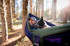Scent detection dog (canis lupus familiaris) Pips and handler Heath Smith relax in a hammock during a day off in Dinkey Creek, California. The team has been surveying for Pacific fisher, which is under consideration as an endangered species.