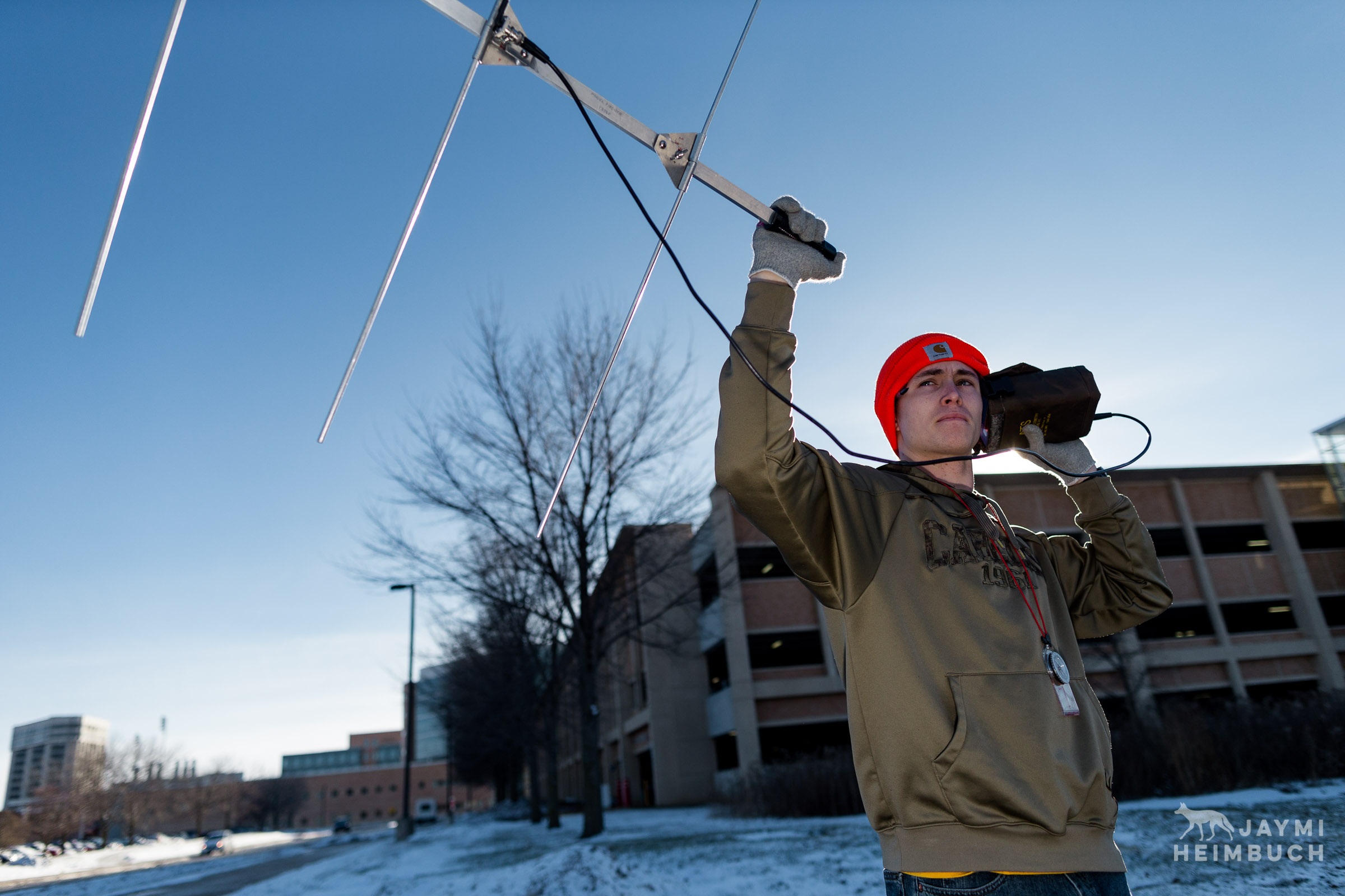 Biology undergraduate student Steven Plesh uses a telemetry pole and receiver to listen for a signal from a nearby radio-collared coyote on the campus of University of Wisconsin-Madison, Madison, Wisconsin.